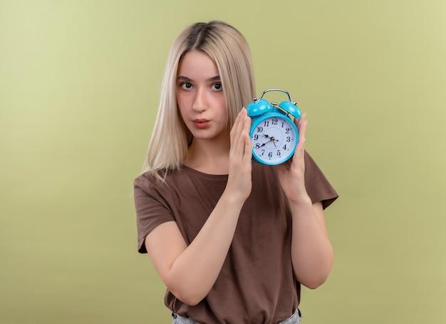 Jovem loira segurando um despertador, olhando para uma parede verde isolada com espaço de cópia