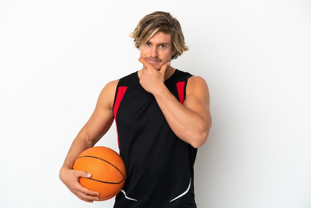 Jovem loira segurando uma bola de basquete isolada no fundo branco pensando