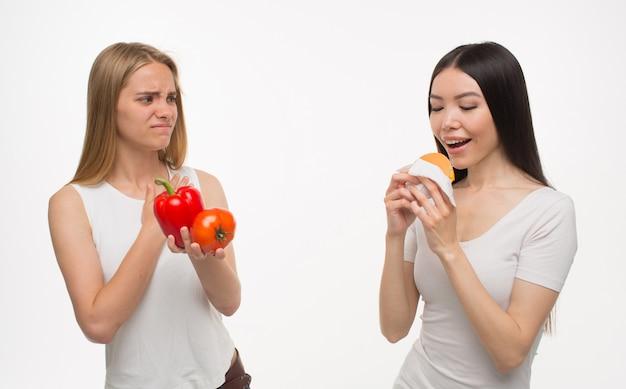Jovem loira segurar legumes saudáveis na mão e olha para sua amiga comendo hambúrguer