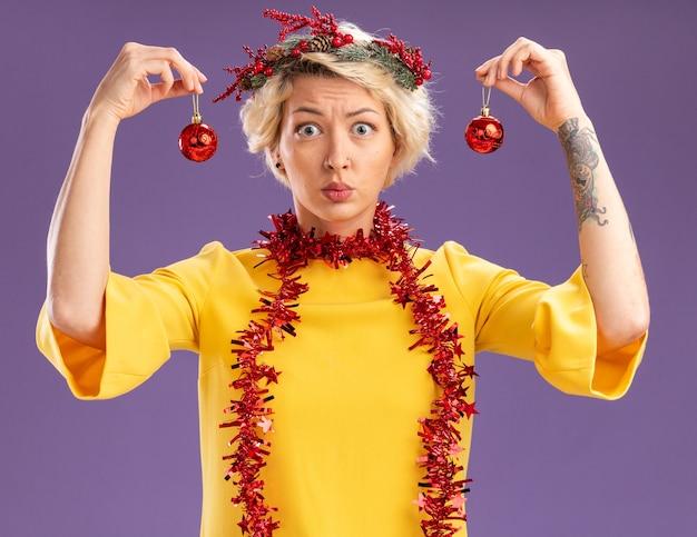 Jovem loira sem noção usando coroa de natal na cabeça e guirlanda de ouropel em volta do pescoço, olhando para a câmera segurando bolas de natal perto da cabeça, isolado no fundo roxo