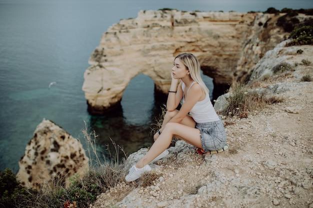 Jovem loira sentada em um penhasco apreciando a vista do mar