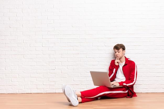 Jovem loira sentada no chão com um laptop