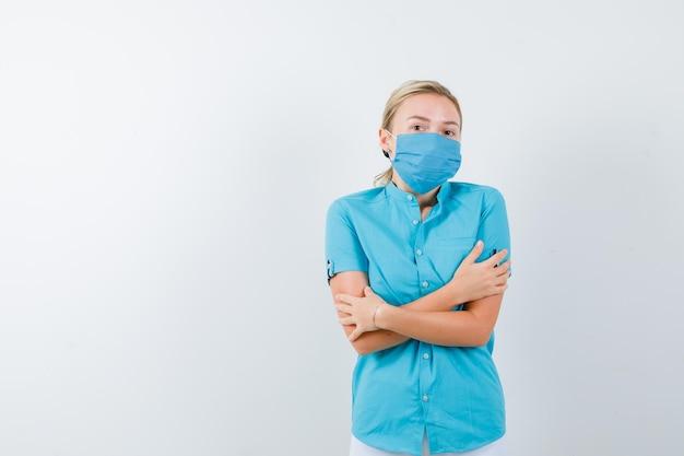 Jovem loira sentindo frio em roupas casuais, máscara e parecendo mal