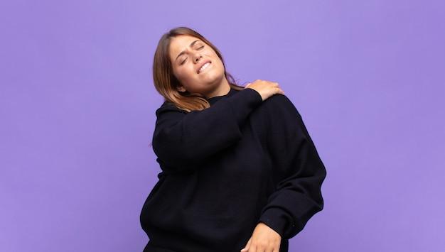Jovem loira sentindo-se cansada, estressada, ansiosa, frustrada e deprimida, sofrendo de dores nas costas ou no pescoço
