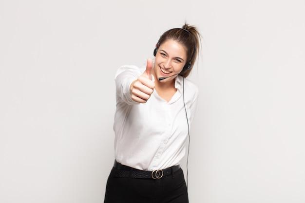 Jovem loira sentindo-se orgulhosa, despreocupada, confiante e feliz, sorrindo positivamente com o polegar para cima