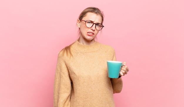 Jovem loira sentindo-se perplexa e confusa, com uma expressão muda e atordoada olhando para algo inesperado. conceito de café
