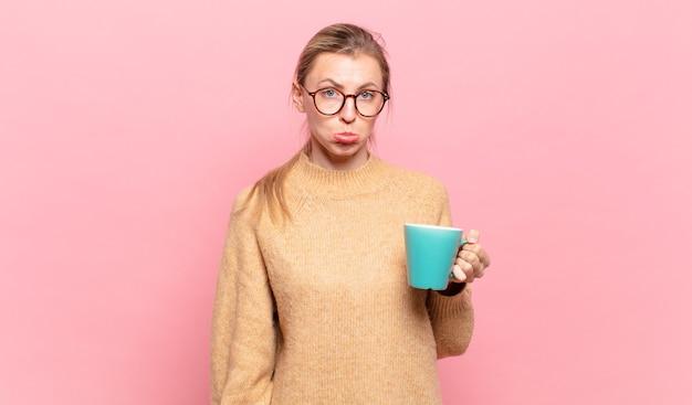 Jovem loira sentindo-se triste e chorona com um olhar infeliz, chorando com uma atitude negativa e frustrada. conceito de café