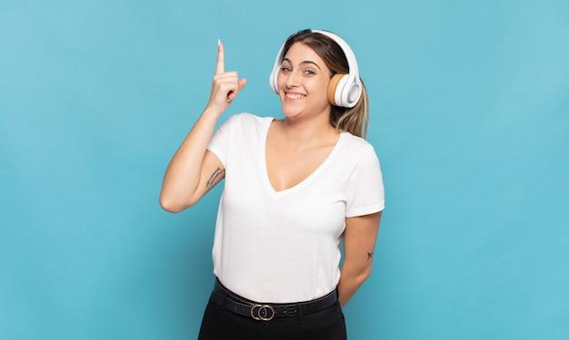 Jovem loira sentindo-se um gênio feliz e animado após realizar uma ideia, levantando alegremente o dedo, eureka!
