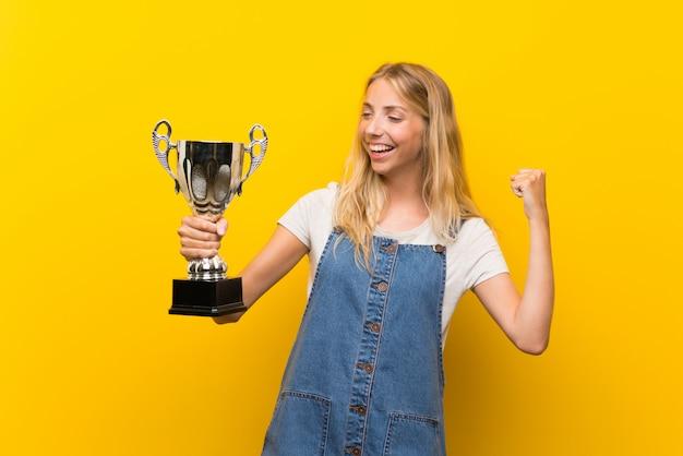 Jovem loira sobre parede amarela isolada, segurando um troféu