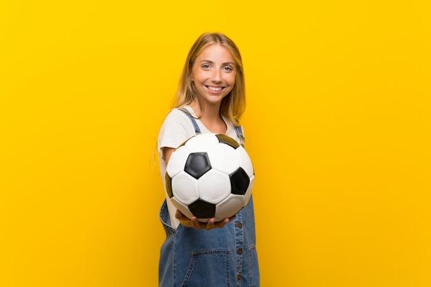Jovem loira sobre parede amarela isolada, segurando uma bola de futebol