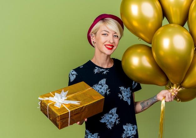 Jovem loira sorridente com chapéu de festa segurando balões e uma caixa de presente, olhando para a frente, isolada na parede verde oliva
