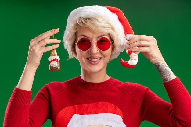 Jovem loira sorridente com chapéu de natal e suéter de natal de papai noel com óculos mostrando boneco de neve e enfeites de natal de papai noel isolados na parede verde