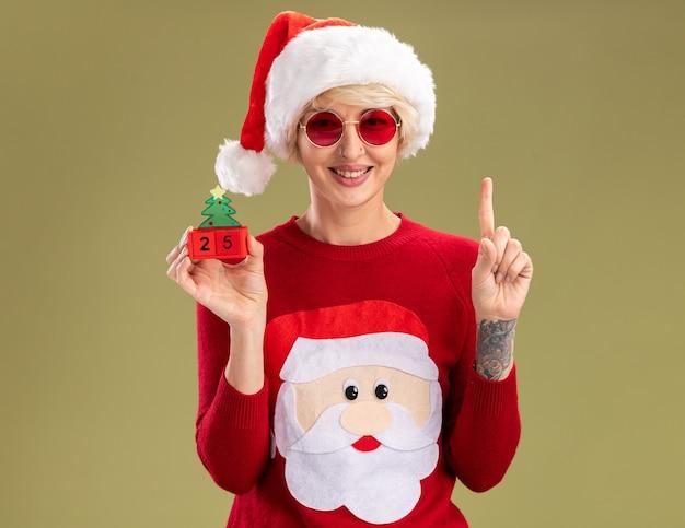 Jovem loira sorridente com chapéu de natal e suéter de natal de papai noel com óculos segurando o brinquedo da árvore de natal com data olhando apontando para cima isolado na parede verde oliva com espaço de cópia