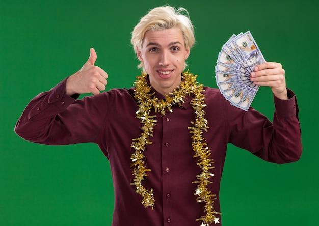 Jovem loira sorridente de óculos com guirlanda de ouropel em volta do pescoço segurando dinheiro olhando para a câmera aparecendo o polegar isolado no fundo verde