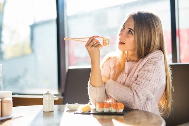 Jovem loira sorridente e ensolarada com um suéter branco comendo sushi no almoço em um pequeno café