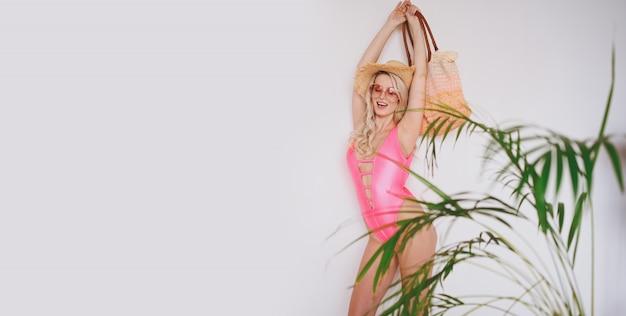 Jovem loira sorridente feliz sexy em um maiô rosa, um chapéu de palha, óculos de sol, animado para apresentar o produto. mulher em um fundo branco com folhas verdes palm.