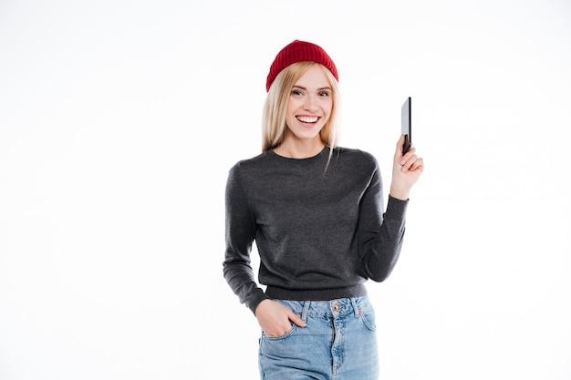 Jovem loira sorridente no chapéu standig e segurando o telefone móvel em branco