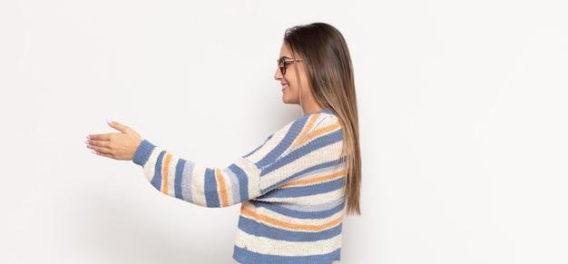 Jovem loira sorrindo, cumprimentando você e dando um aperto de mão para fechar um negócio de sucesso, o conceito de cooperação