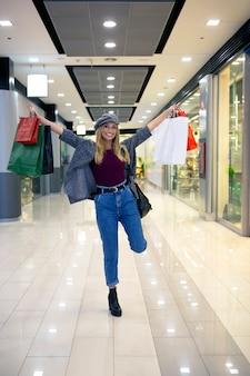 Jovem loira sorrindo e levantando suas sacolas de compras feitas no shopping