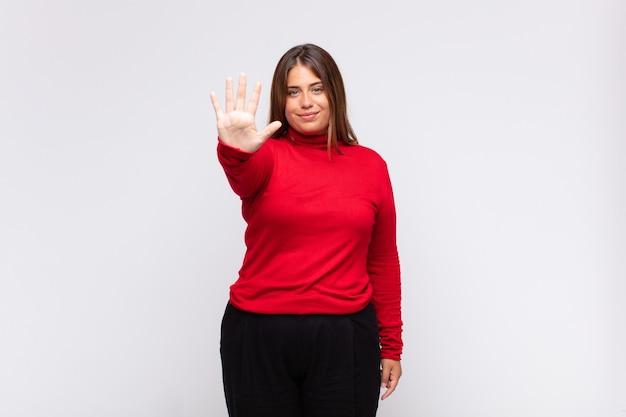 Jovem loira sorrindo e parecendo amigável, mostrando o número cinco ou quinto com a mão para a frente, em contagem regressiva