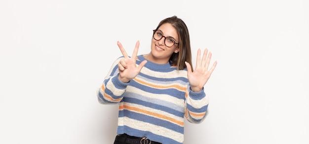 Jovem loira sorrindo e parecendo amigável, mostrando o número oito ou oitavo com a mão para a frente, em contagem regressiva