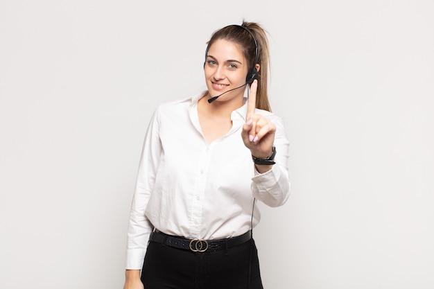 Jovem loira sorrindo e parecendo amigável, mostrando o número um ou primeiro com a mão para a frente, em contagem regressiva Foto Premium