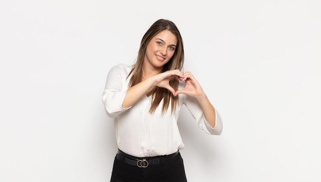 Jovem loira sorrindo e se sentindo feliz, fofa, romântica e apaixonada, fazendo formato de coração com as duas mãos