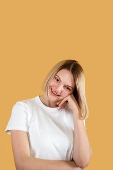 Jovem loira sorrindo isolada em amarelo