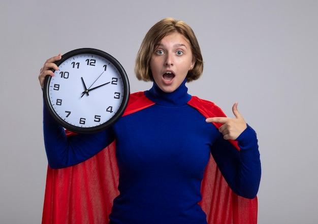Jovem loira super-heroína impressionada com uma capa vermelha, olhando para a frente, segurando e apontando para o relógio isolado na parede branca