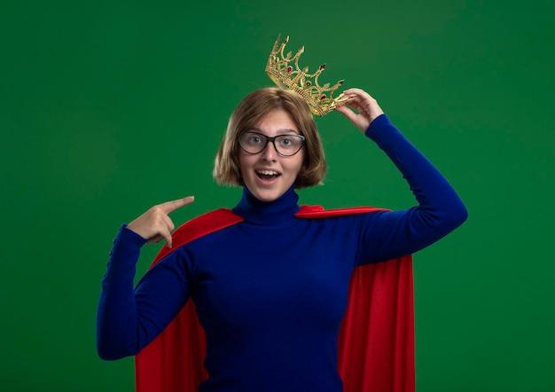Jovem loira super-heroína impressionada com uma capa vermelha usando óculos e uma coroa, agarrando uma coroa, olhando para a frente e apontando para si mesma, isolada na parede verde