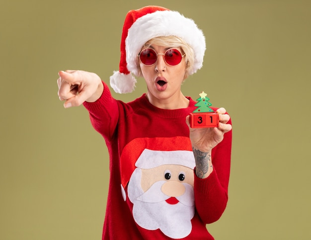 Jovem loira surpresa com chapéu de natal e suéter de natal de papai noel com óculos segurando o brinquedo da árvore de natal com data olhando e apontando para o lado isolado na parede verde oliva com espaço de cópia