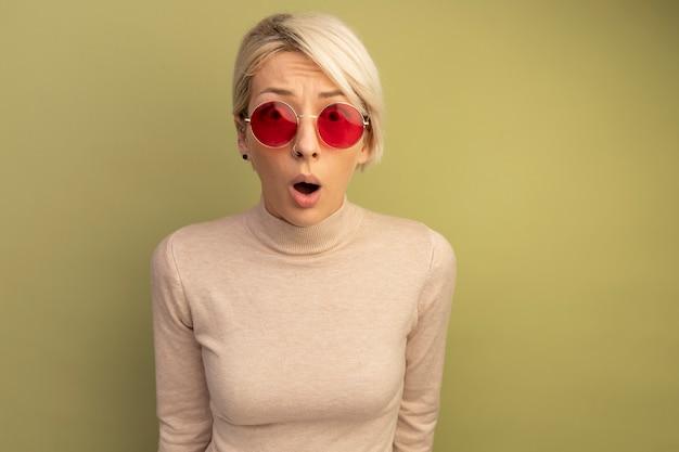 Jovem loira surpresa com óculos escuros, olhando para a frente, isolada na parede verde oliva com espaço de cópia