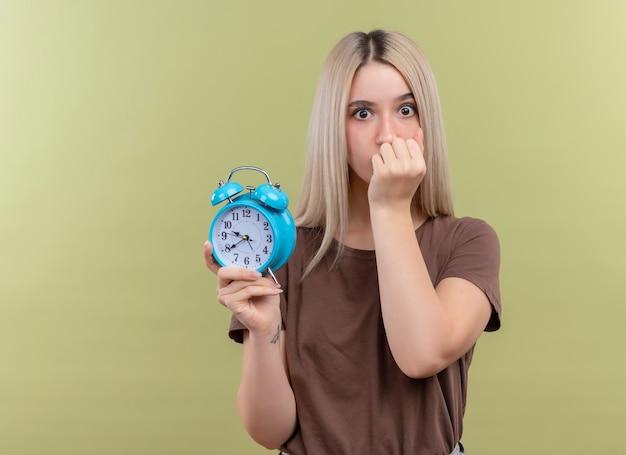 Jovem loira surpresa segurando o despertador com a mão na boca na parede verde isolada com espaço de cópia