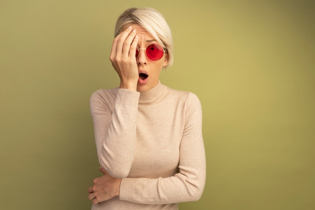 Jovem loira surpresa usando óculos escuros cobrindo metade do rosto com a mão parecendo isolada em uma parede verde oliva com espaço de cópia