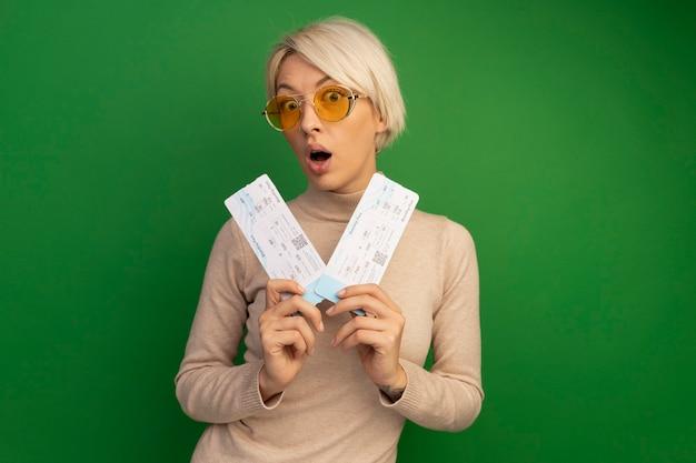 Jovem loira surpresa usando óculos escuros segurando passagens de avião isoladas em uma parede verde com espaço de cópia