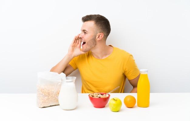 Jovem loira tomando café da manhã gritando com a boca aberta
