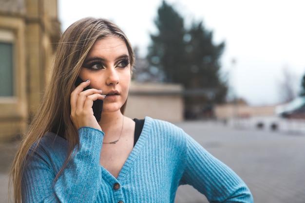 Jovem loira tomando um celular na rua