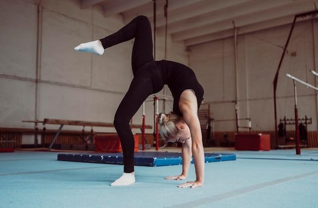 Jovem loira treinando para as olimpíadas de ginástica