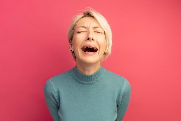 Jovem loira triste chorando com os olhos fechados, isolada na parede rosa com espaço de cópia