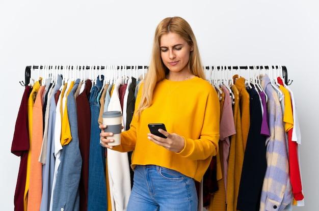 Jovem loira uruguaia em uma loja de roupas segurando café para levar e um celular