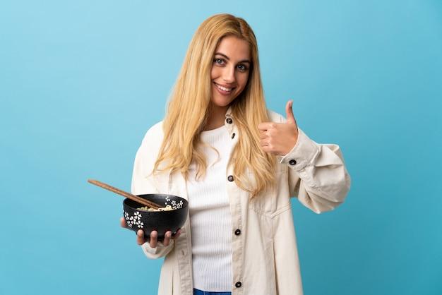 Jovem loira uruguaia sobre azul isolado com polegares para cima, porque algo de bom aconteceu enquanto segura uma tigela de macarrão com pauzinhos
