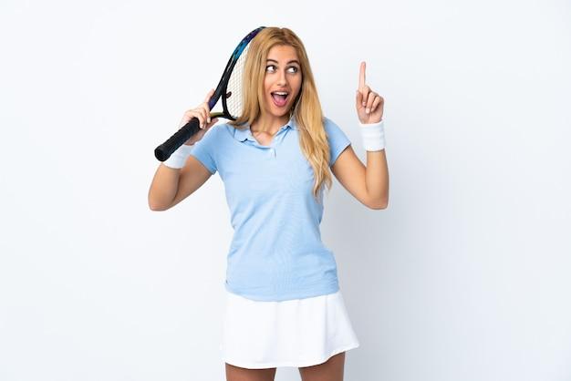 Jovem loira uruguaia sobre branco isolado jogando tênis e apontando para cima