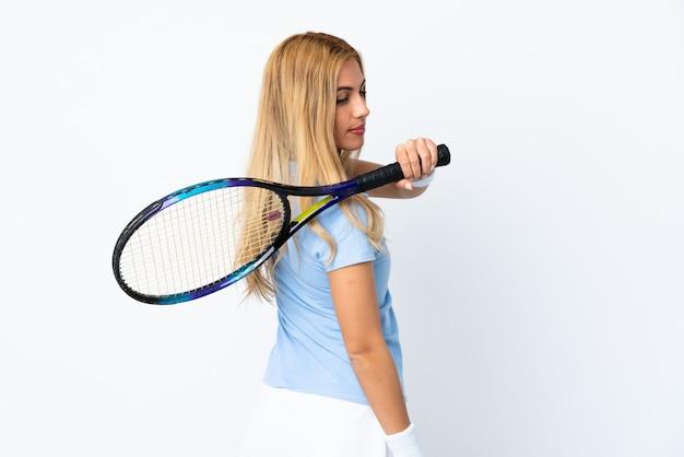 Jovem loira uruguaia sobre branco isolado jogando tênis
