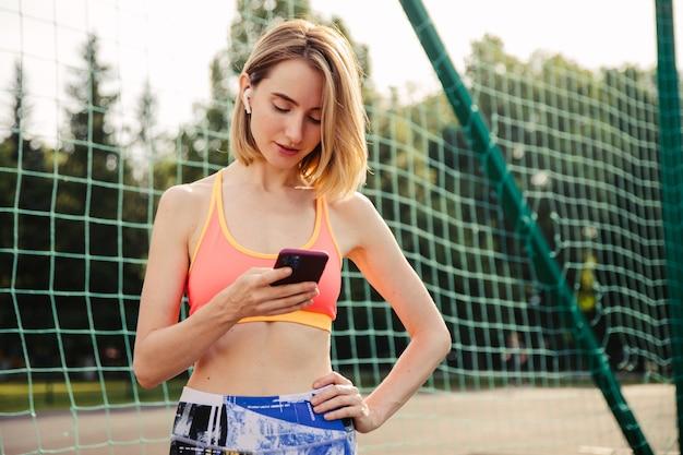 Jovem loira usa smartphone no campo de atletismo