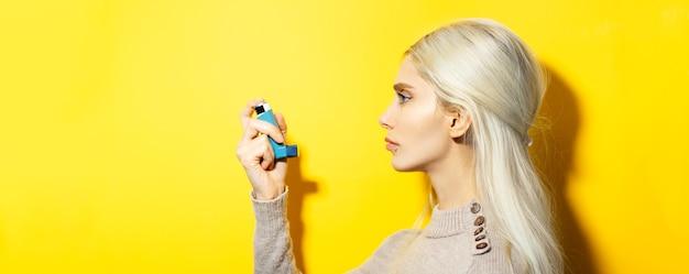 Jovem loira, usando máscara médica contra a gripe e suéter bege, segurando o inalador asmático na mão na parede amarela.