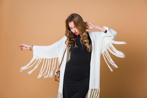 Jovem loira usando um poncho de franja branca enorme e um vestido longo cinza dançando