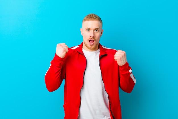 Jovem loira, vestindo roupas esportivas, gritando agressivamente com uma expressão de raiva ou com os punhos cerrados, comemorando o sucesso