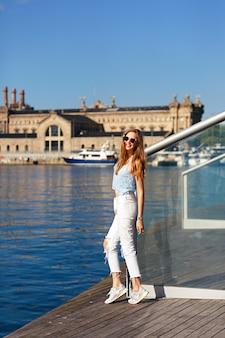 Jovem loira viaja em barcelona, com roupas elegantes e óculos escuros, vista deslumbrante sobre o mar e arquitetura.