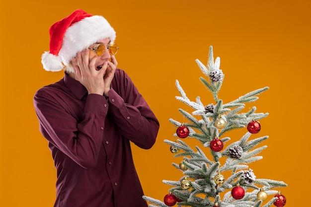 Jovem loiro animado com chapéu de papai noel e óculos em pé perto da árvore de natal decorada, com as mãos no rosto olhando para baixo, isolado em um fundo laranja