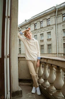 Jovem loiro bonito com suéter bege posando na varanda